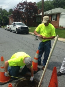 Hydrostructures employees inspecting a manhole.
